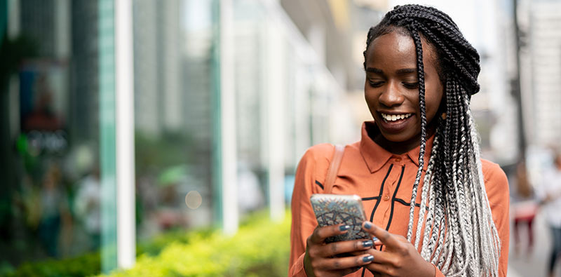 woman smiling while using her mobile phone
